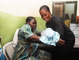 Tiwa Savage with a mother and new born in the hospital