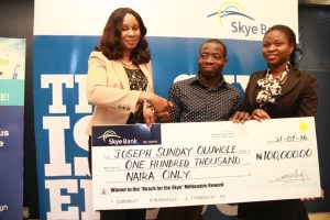 """L-R: Head, Retail Banking, Skye Bank Plc, Nkolika Okoli; Lucky Winner of the N100, 000 Category (GSM Engineer), Joseph Sunday Oluwole; Marketer, Retail Banking, Iju Branch, Skye Bank Plc, Abosede Oluwaseun Ogunbo at the seventh cheque presentation to winners in the ongoing Skye Bank's """"Reach for the Skye"""" Millionaire Reward Scheme held in Lagos recently"""
